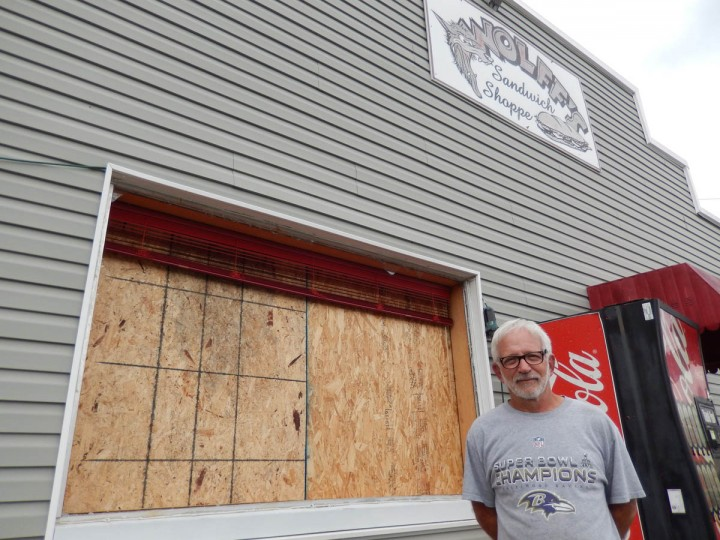 Baltimore native Ron Wolff stands in front of his restaurant, Wolff's Sandwich Shoppe, in Atlantic, Va. The front window of Wolff's store was blown out after the Antares rocket explosion on Tuesday at nearby Wallops Island, Va. Wolff's store was about four miles away from the launch site. (Eduardo A. Encina, Baltimore Sun)