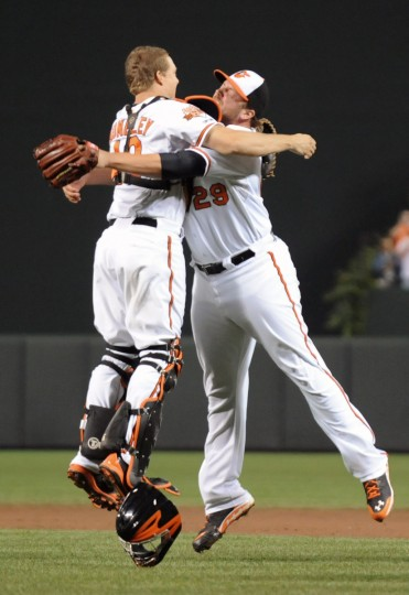 Orioles catcher Nick Hundley, left, leaps into the arms of pitcher Tommy Hunter after the O's recorded the last out to clinch the American League East in September 2014. (Kenneth K. Lam/Baltimore Sun)