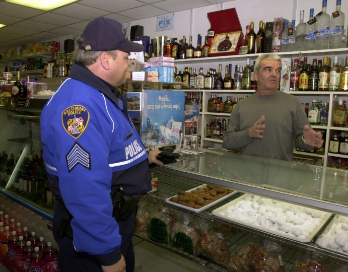 2/28/02: In an effort to revitalize the Greektown community, John E. Gavrilis, exective director of the Greektown Community Development Corporation and former Baltimore City Police Col., has implemented a safety initiative that employs off-duty city police officers to walk foot patrols in the community until 10 p.m. Baltimore City Police Sgt. Bob Wehner, left, talks with Angelo Theofanidis, right, owner of Athena Fine Greek Imports, during patrol. (Kenneth K. Lam/Baltimore Sun)