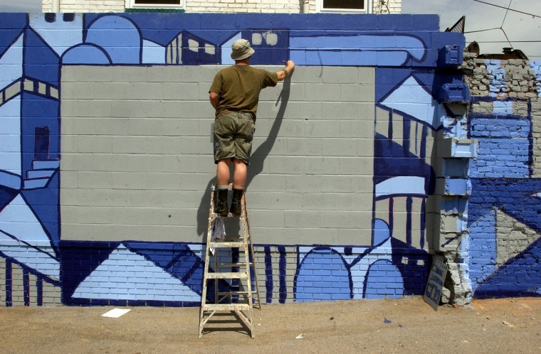 4/20/04: Shawn McRaney begins to paint a mural in Greektown on Oldham Street south of Eastern Avenue Tuesday, April 20, 2004. He and three other artists are participating in the mural. (Nanine Hartzenbusch/Baltimore Sun)