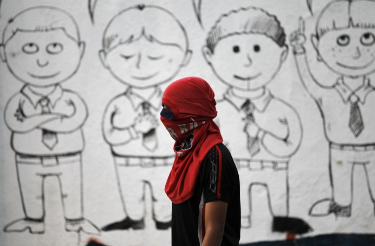 A protester stands in front of a mural of school students on the wall of a local high school during a protest in support of the Saudi Shi'ite scholar Nimar Al Nimar, in the village of Jidhafs west of Manama. Shi'ites from Bahrain have been protesting in solidarity with Nimar Al Nimar who has been given death sentence by the Saudi authorities. (Hamad I Mohammed/Reuters)