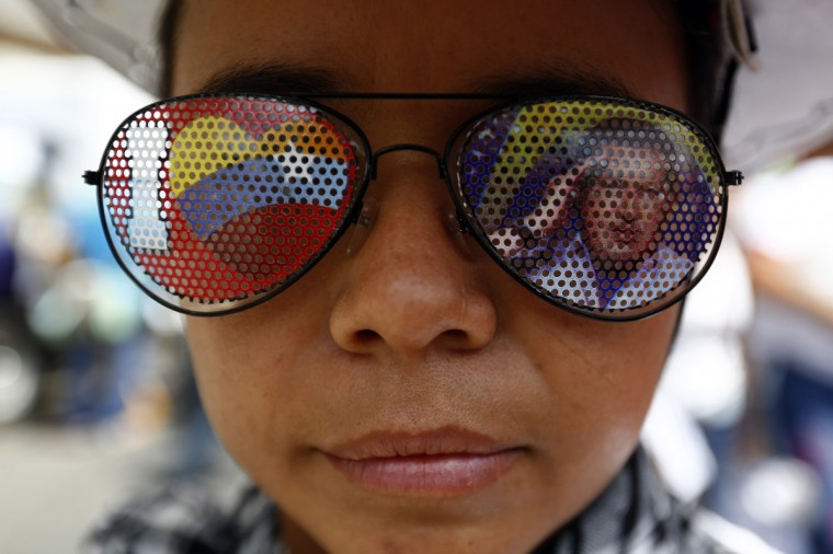A supporter of Venezuela's President Nicolas Maduro wears a pair of sunglasses with a picture of late Venezuelan president Hugo Chavez, during a rally in support of Maduro in Caracas. Both supporters and detractors of Venezuela's government marched through the capital Caracas on Saturday. Supporters of Maduro were protesting this month's killing of a young 'Chavista' lawmaker, a crime the government has blamed on political opponents, including Colombian paramilitary forces. Separately, the opposition demonstrated against a laundry list of issues, including a slumping economy, shortages of basic goods, and sky-high crime rates. (Jorge Silva/Reuters)