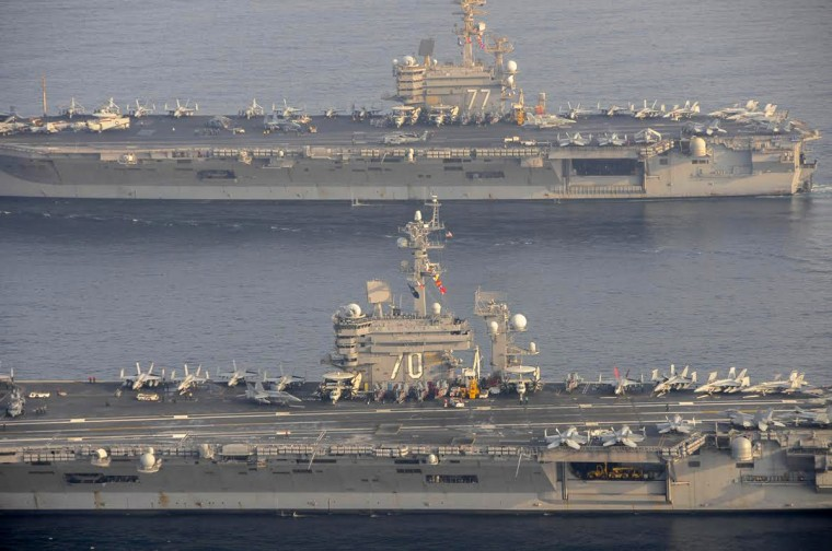 The U.S. Navy aircraft carrier USS Carl Vinson (CVN 70), bottom, is seen relieving the USS George H.W. Bush in the Arabian Gulf. George H.W. Bush will soon depart the U.S. 5th Fleet area of responsibility for its homeport at Norfolk, Virginia, and Carl Vinson will take over support of maritime security operations, strike operations in Iraq and Syri.a (US Navy/Mass Communication Specialist 2nd Class Korrin Kim/Handout via Reuters)