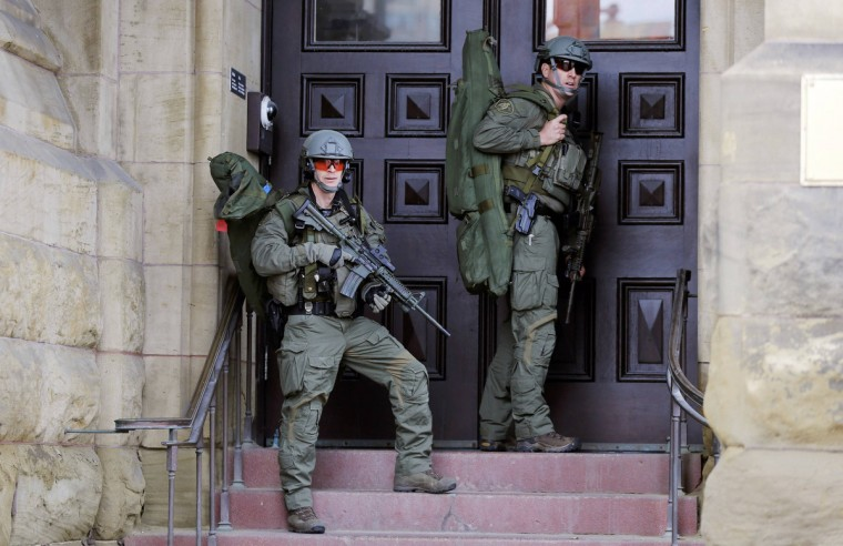 Armed RCMP officers guard the front of Langevin Block on Parliament Hilll following a shooting incident in Ottawa October 22, 2014. A Canadian soldier was shot at the Canadian War Memorial and a shooter was seen running towards the nearby parliament buildings, where more shots were fired, according to media and eyewitness reports. (Chris Wattie/Reuters)
