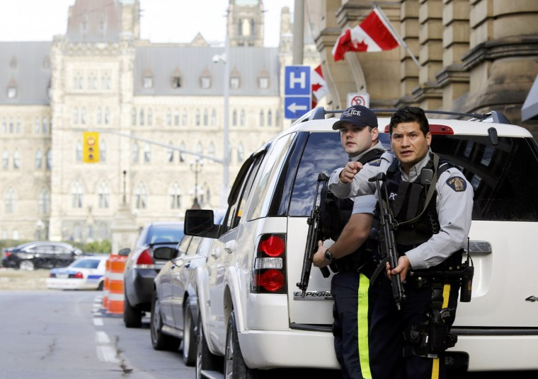 Armed RCMP officers guard access to Parliament Hill following a shooting incident in Ottawa October 22, 2014. A Canadian soldier was shot at the Canadian War Memorial and a shooter was seen running towards the nearby parliament buildings, where more shots were fired, according to media and eyewitness reports. (Chris Wattie/Reuters)