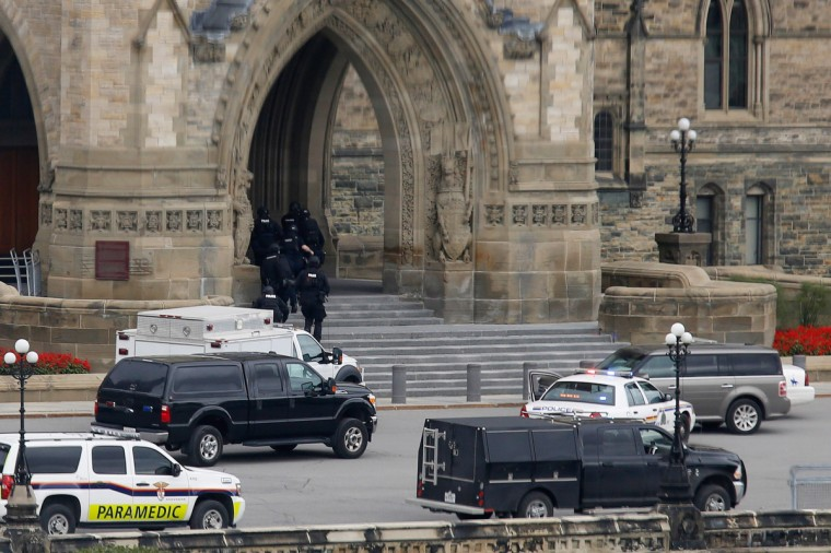 Armed RCMP officers head in to Centre Block on Parliament Hill following a shooting incident in Ottawa October 22, 2014. A Canadian soldier was shot at the Canadian War Memorial and a shooter was seen running towards the nearby parliament buildings, where more shots were fired, according to media and eyewitness reports. (Chris Wattie/Reuters)