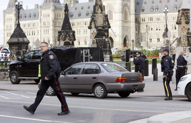 Police guard a car on Parliament Hill thought to be the car of one of the suspects in a shooting incident in Ottawa October 22, 2014. A Canadian soldier was shot at the Canadian War Memorial and a shooter was seen running towards the nearby parliament buildings, where more shots were fired, according to media and eyewitness reports. (Chris Wattie/Reuters)