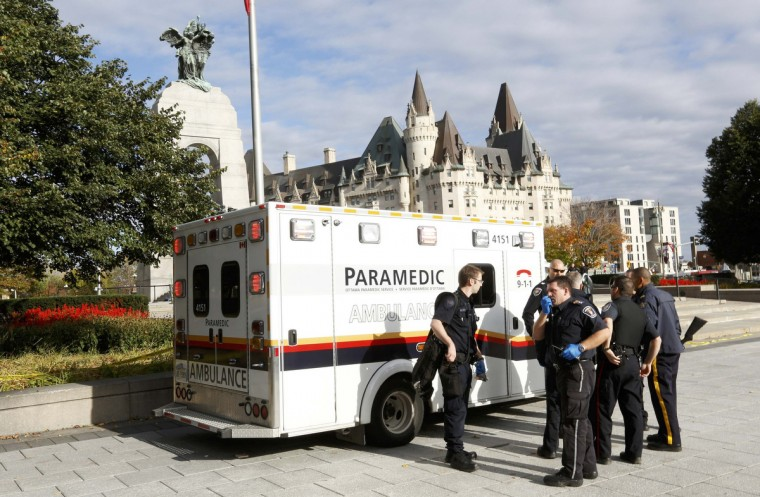 Police officers and ambulance workers gather alongside the Canadian War Memorial following a shooting incident in Ottawa October 22, 2014. A Canadian soldier was shot at the Canadian War Memorial and a shooter was seen running towards the nearby parliament buildings, where more shots were fired, according to media and eyewitness reports. (Chris Wattie/Reuters)
