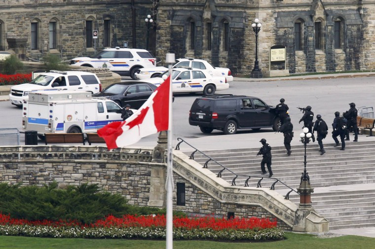 Armed RCMP officers approach Centre Block on Parliament Hill following a shooting incident in Ottawa October 22, 2014. A Canadian soldier was shot at the Canadian War Memorial and a shooter was seen running towards the nearby parliament buildings, where more shots were fired, according to media and eyewitness reports. (Chris Wattie/Reuters)