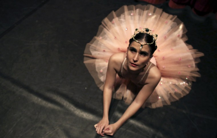 Blind student Marina Gimaraes of the Association of Ballet and Arts for the Blind, warms up backstage before performing 'Corsario' e 'Paquitas' during celebrations marking Brazil's Children's Day at the Italo Theater in Sao Paulo October 12, 2014. The Association was founded by Brazilian ballerina and physiotherapist Fernanda Bianchini in 1995, when she decided to teach classical ballet to the blind for free. Since then, her classes have been opened to the deaf and mute, and even to children and youths with other handicaps. Bianchini says that the school's main goal for their students is for them to improve their posture, balance, spatial sense and self-esteem, in addition to breaking barriers and prejudices about people with handicaps. (Nacho Doce/Reuters)
