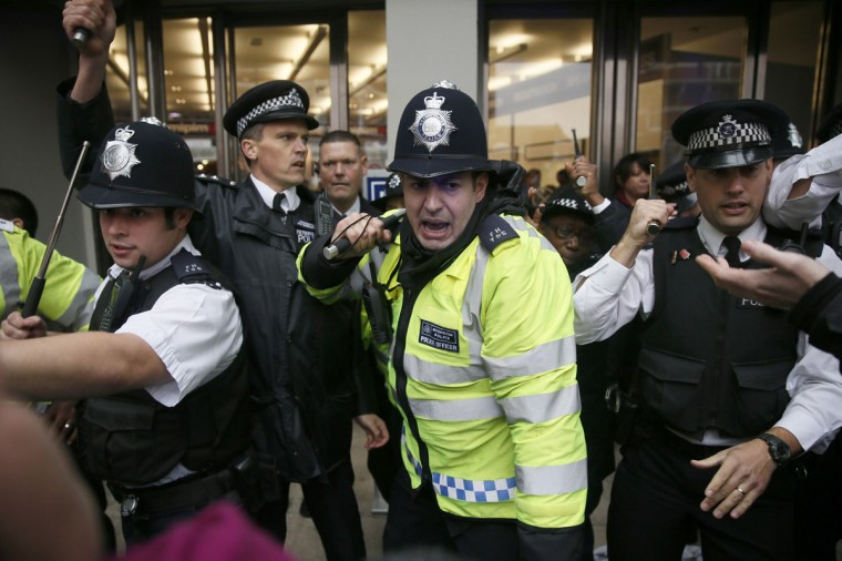 Police officers scuffle with demonstrators outside the MIPIM property fair at Olympia in London October 15, 2014. The fair, which aims to bring together participants in the international property market, was addressed by London Mayor Boris Johnson. (REUTERS/Stefan Wermuth)