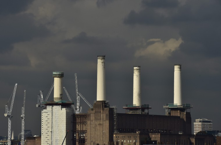 A rig (L) surrounds the top of one of the chimneys of Battersea Power Station as demolition work is carried out, in London October 2, 2014. Developers are demolishing the art deco landmark's corroded chimneys and will replace them with replicas, as part of the re-development of the area. (Toby Melville/Reuters)