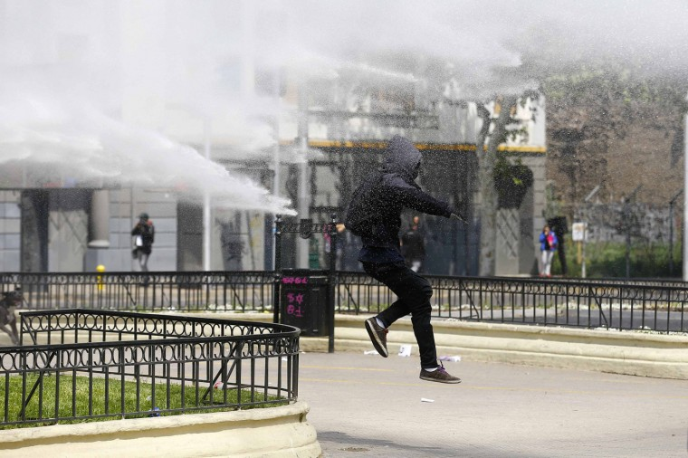 A student protester runs from a jet of water released from a riot police vehicle during a demonstration against the government to demand changes and an end to profiteering in the education system in Santiago October 9, 2014. (Ivan Alvarado/Reuters)