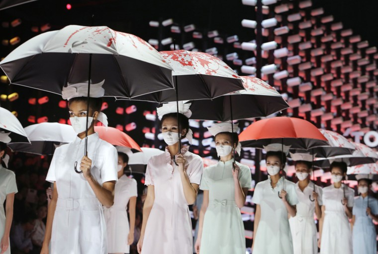 Models wearing masks hold umbrellas as they perform during the TORAY Liu Wei Collection segment at China Fashion Week in Beijing, October 30, 2014. REUTERS/Jason Lee