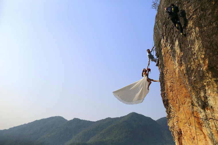 Zheng Feng, an amateur climber takes wedding pictures with his bride on a cliff in Jinhua, Zhejiang province, October 26, 2014. Picture taken October 26, 2014. (China Daily /Reuters)