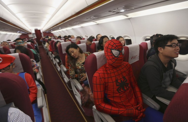 A Lucky Air crew member dressed as Spiderman (3rd R) during an onboard Halloween celebration sits next to passengers during a flight from Kunming to Shenzhen, in Kunming, October 31, 2014. Attendants of the domestic Lucky Air flight on Friday night dressed themselves in costumes of superheroes and movie figures to serve their customers as well as celebrate Halloween, according to local media. (Wong Campion/Reuters)