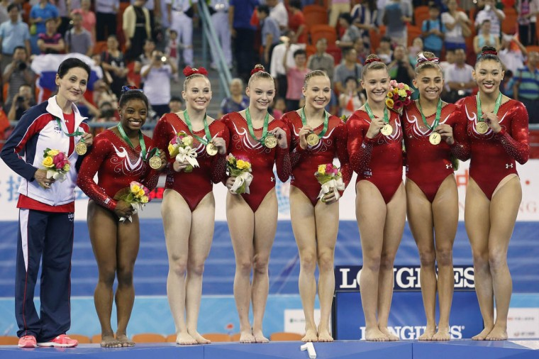 U.S. gymnasts pose with their gold medals on the podium after winning the women's team final event at the 2014 World Artistic Gymnastics Championships in Nanning, Guangxi Zhuang Autonomous Region, October 8, 2014. The United States defended their women's team title at the championships on Wednesday with a victory over hosts China, with Russia claiming third. (China Daily/Reuters photo)