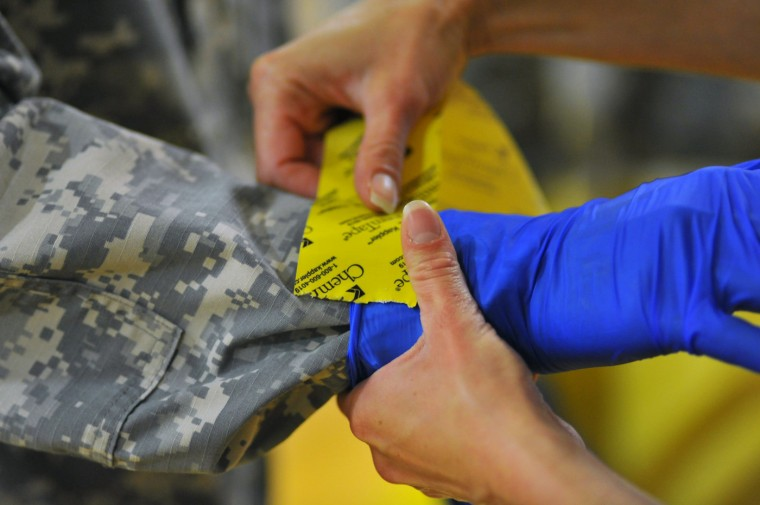Ondraya Frick from U.S. Army Medical Research Institute of Infectious Diseases (USAMRIID) demonstrates how to properly apply tape to gloves for U.S. Army soldiers from the 101st Airborne Division (Air Assault), who are earmarked for the fight against Ebola, before their deployment to West Africa, at Fort Campbell, Kentucky October 9, 2014. (Harrison McClary/Reuters)