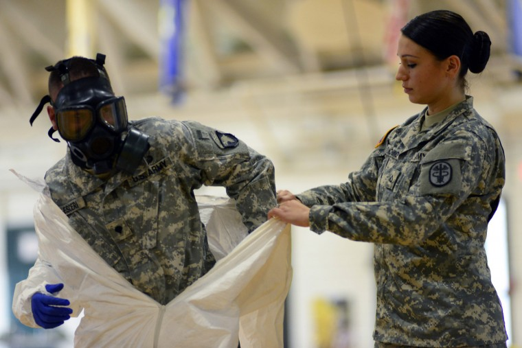 Pfc. Kaiya Capuchino from U.S. Army Medical Research Institute of Infectious Diseases (USAMRIID) trains US Army soldiers from the 101st Airborne Division (Air Assault), who are earmarked for the fight against Ebola, before their deployment to West Africa, at Fort Campbell, Kentucky October 9, 2014. (Harrison McClary/Reuters)