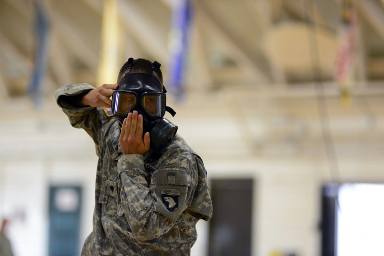 A U.S. Army soldier from the 101st Airborne Division (Air Assault), who are earmarked for the fight against Ebola, learns how to put on a protective mask before their deployment to West Africa, at Fort Campbell, Kentucky October 9, 2014. (Harrison McClary/Reuters)
