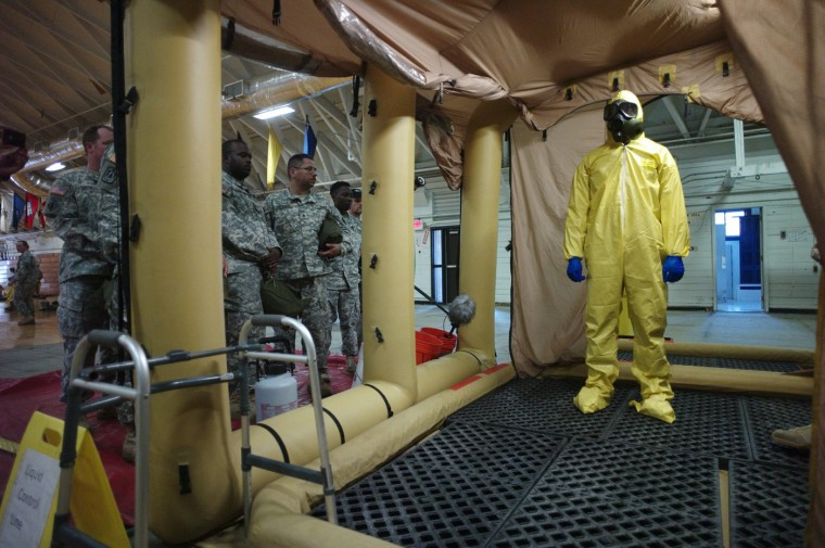 A soldier goes through the decontamination process with U.S. Army soldiers from the 101st Airborne Division (Air Assault), who are earmarked for the fight against Ebola, take part in training before their deployment to West Africa, at Fort Campbell, Kentucky October 9, 2014. (Harrison McClary/Reuters)