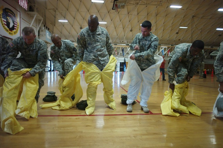 U.S. Army soldiers from the 101st Airborne Division (Air Assault), who are earmarked for the fight against Ebola, put on protective suits during training before their deployment to West Africa, at Fort Campbell, Kentucky October 9, 2014. (Harrison McClary/Reuters)