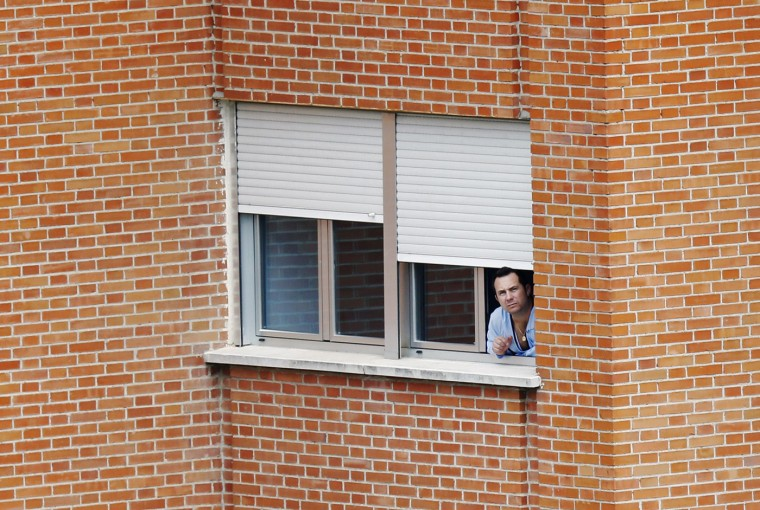 Javier Limon, the husband of Spanish nurse Teresa Romero Ramos who contracted Ebola, looks out of the window of a ward he is being kept isolated in, at Madrid's Carlos III hospital, October 9, 2014. The health of Teresa Romero Ramos worsened on Thursday and four other people were put into isolation in Madrid, while the government rejected claims that its methods for dealing with the disease weren't working, and blamed human error. (Susana Vera/Reuters)