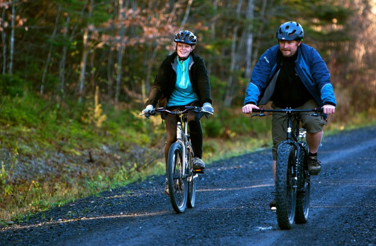 Kaci Hickox (L) and boyfriend Ted Wilbur go for a bike ride in Fort Kent, Maine October 30, 2014. Hickox, who treated Ebola patients in Sierra Leone but has tested negative for the virus, ventured out of her home Thursday, defying a Maine quarantine order and setting up a legal collision with state authorities. REUTERS/Ashley L. Conti/Bdn