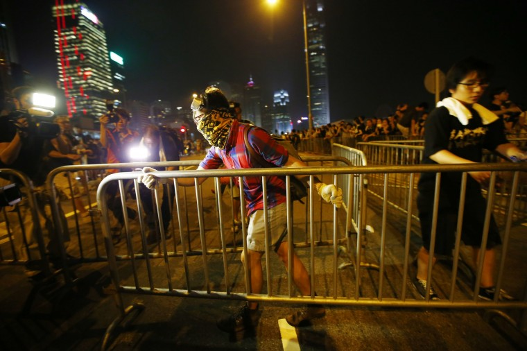 A protester carries a metal fence as he tries to block an avenue outside the offices of Hong Kong's Chief Executive Leung Chun-ying in Hong Kong October 2, 2014. Hong Kong authorities on Thursday urged thousands of pro-democracy protesters to immediately end their blockade of the city centre and said any attempt to occupy administrative buildings would be met with a resolute and firm response. (Carlos Barria/Reuters)