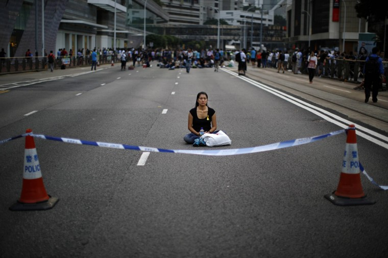 A woman meditates at a protest site after clashes between anti-occupy Central demonstrators and pro-democracy protesters near the government headquarters in Hong Kong, October 13, 2014. Hundreds of unidentified people, some wearing masks, tried to break down protest barriers in the heart of Hong Kong's business district on Monday, scuffling with protesters who have occupied the streets for the past two weeks. (Carlos Barria/Reuters)