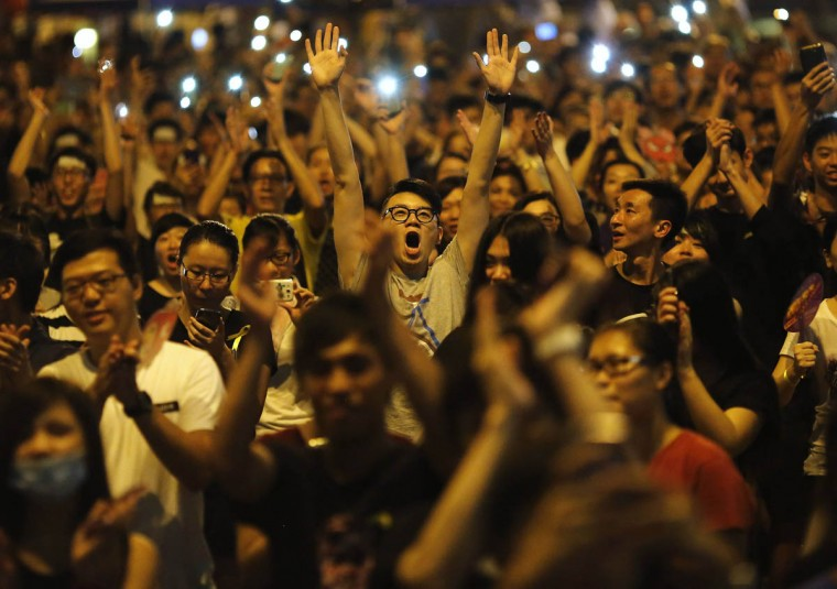 Protesters react as Joshua Wong (not pictured), leader of the student movement, speaks to the crowd outside the government headquarters building in Hong Kong. Thousands of pro-democracy protesters thronged the streets of Hong Kong on Wednesday, some of them jeering National Day celebrations, and students threatened to ramp up demonstrations if the city's pro-Beijing leader did not step down. (Carlos Barria/Reuters)