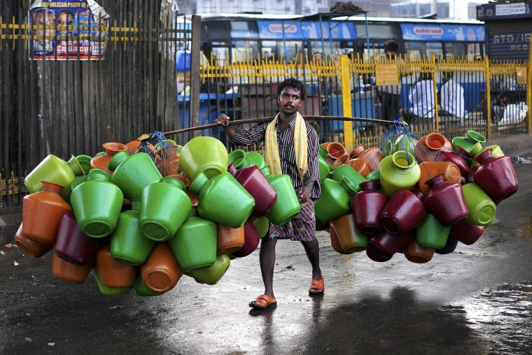 A man carries empty water pitchers for sale in a market in the southern Indian city of Bangalore October 9, 2014. (Abhishek N. Chinnappa/Reuters)
