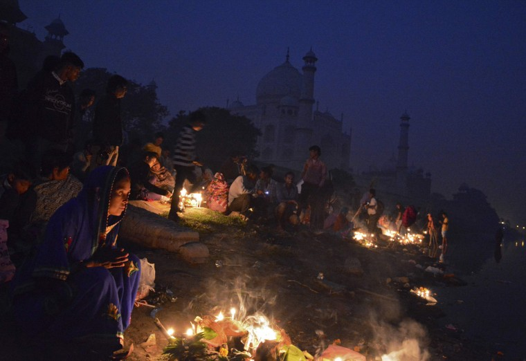 Hindu devotees worship the Sun god Surya against the backdrop of the historic Taj Mahal during the Hindu religious festival of Chatt Puja in the northern Indian city Agra October 30, 2014. Hindu women fast for the whole day for the betterment of their family and the society during the festival. REUTERS/Brijesh Singh