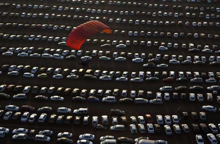 A glider flies over a parking lot in northern Israel's Jezreel Valley during an international hot air balloon festival October 14, 2014. (REUTERS/Nir Elias)