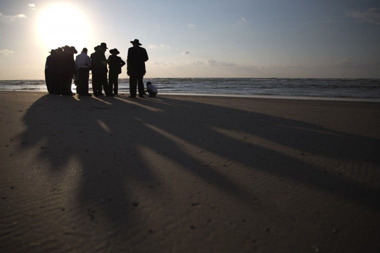 Ultra-orthodox Jews pray at a Tel Aviv beach before emptying their pockets during the Jewish New Year ritual of Tashlich, October 2, 2014. Tashlich is a ritual of casting away sins of the past year into the water ahead of Yom Kippur, the Jewish Day of Atonement, which starts at sundown Friday. (Finbarr O'Reilly/Reuters)