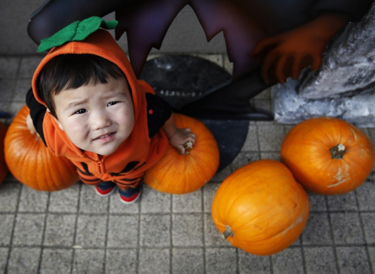 Two-year-old Shunto, wearing a Halloween outfit, sits on pumpkins before a Halloween parade in Kawasaki, south of Tokyo, October 26, 2014. More than 100,000 spectators turned up to watch the parade, where 2,500 participants dressed up in costumes, according to the organizer. (Yuya Shino/Reuters)