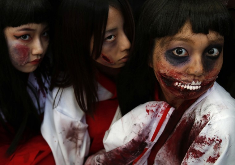Participants in costumes pose for pictures after a Halloween parade in Kawasaki, south of Tokyo, October 26, 2014. More than 100,000 spectators turned up to watch the parade, where 2,500 participants dressed up in costumes, according to the organizer. (Yuya Shino/Reuters)