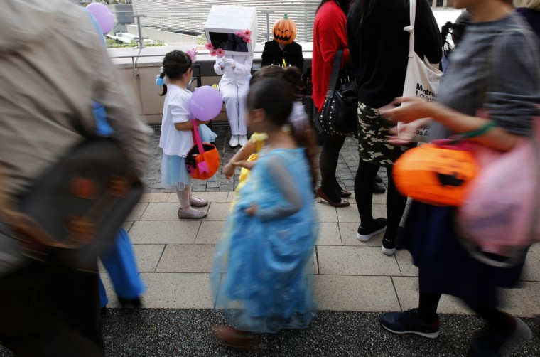 Participants in costumes give candies to children during a Halloween parade in Kawasaki, south of Tokyo, October 26, 2014. More than 100,000 spectators turned up to watch the parade, where 2,500 participants dressed up in costumes, according to the organizer. (Yuya Shino/Reuters)