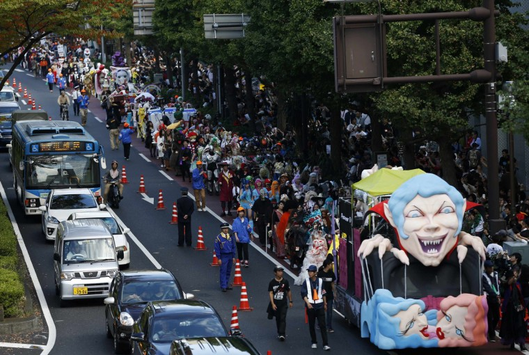 Participants wearing costumes walk behind a float during a Halloween parade in Kawasaki, south of Tokyo, October 26 2014. More than 100,000 spectators turned up to watch the parade, where 2,500 participants dressed up in costumes, according to the organizer. (Yuya Shino/Reuters)