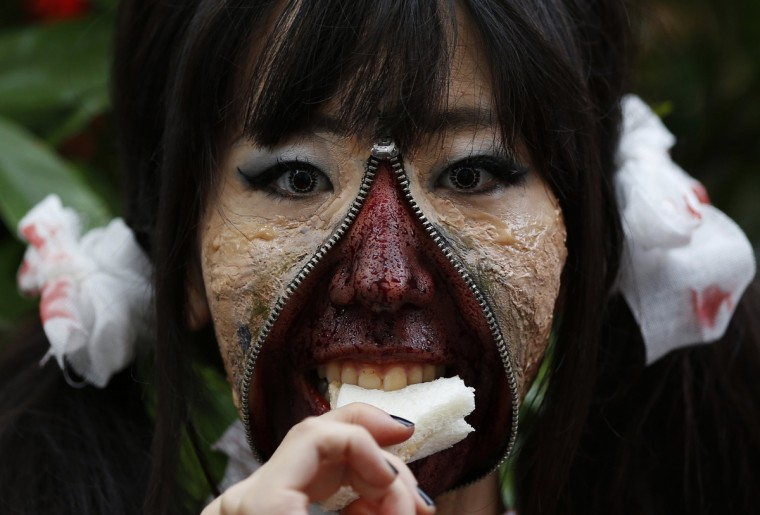 A participant in costume eats a sandwich after a Halloween parade in Kawasaki, south of Tokyo, October 26, 2014. More than 100,000 spectators turned up to watch the parade, where 2,500 participants dressed up in costumes, according to the organizer. (Yuya Shino/Reuters)