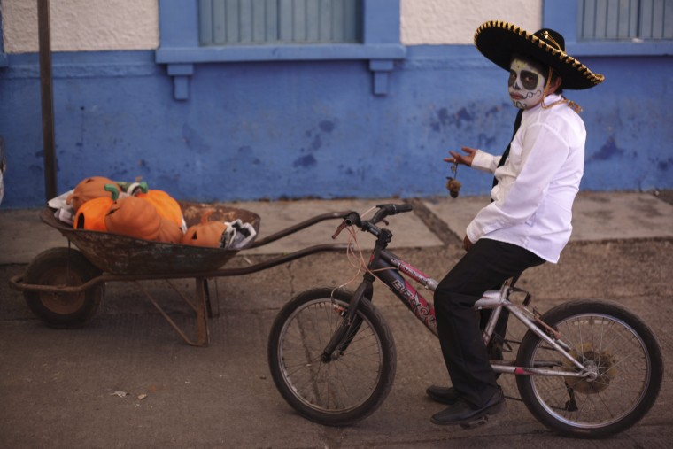 "A boy with his face painted as a skull poses for a photo during the start of the ""Las Catrinas"" festival, ahead of the Day of the Dead in Cupula on the outskirts of Morelia , October 26, 2014. La Catrina is a popular figure in Mexico known as ""The Elegant Skull"". The annual Day of the Dead is observed on November 1 and 2. (Alan Ortega/Reuters)"