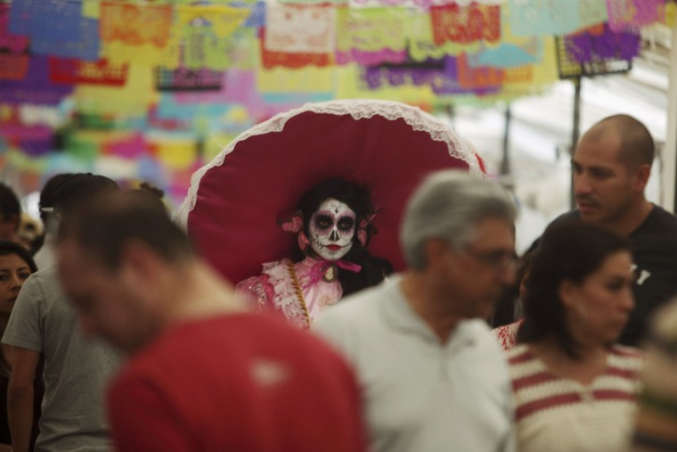"A woman with her face painted as a skull attends the start of the ""Las Catrinas"" festival, ahead of the Day of the Dead in Cupula on the outskirts of Morelia , October 26, 2014. La Catrina is a popular figure in Mexico known as ""The Elegant Skull"". The annual Day of the Dead is observed on November 1 and 2. (Alan Ortega/Reuters)"