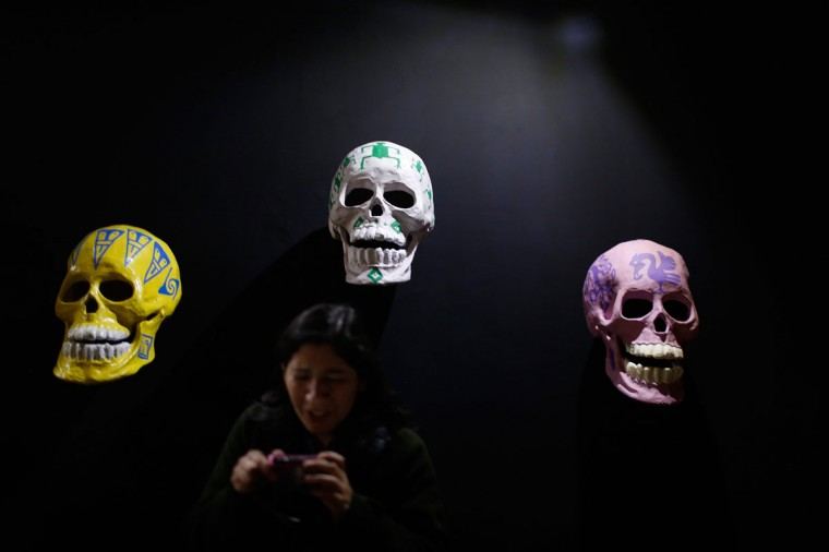 A woman checks a picture on her camera while standing in front of skulls, which form part of an art installation to celebrate the Day of the Dead, in Zocalo Square, Mexico City. (Tomas Bravo/Reuters)