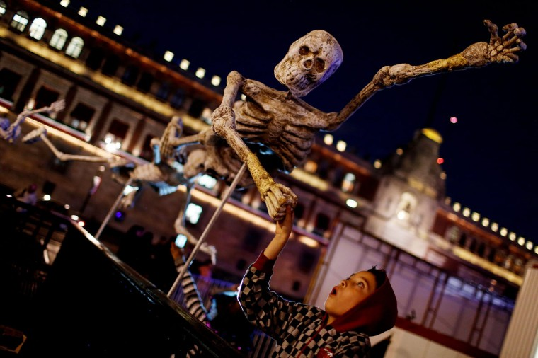 A child reacts while touching a skeleton model, which is part of an art installation to celebrate the Day of the Dead, in Zocalo Square, Mexico City. (Tomas Bravo/Reuters)