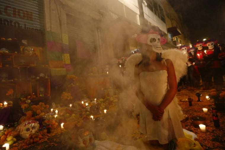 Sex workers wear skeleton masks, a traditional Mexican symbol representing the Day of the Dead, as they make an offering during a procession to remember their deceased colleagues, especially those who were violently murdered, in Mexico City October 27, 2014. The annual Day of the Dead is observed on November 1 and 2. (Edgard Garrido/Reuters)