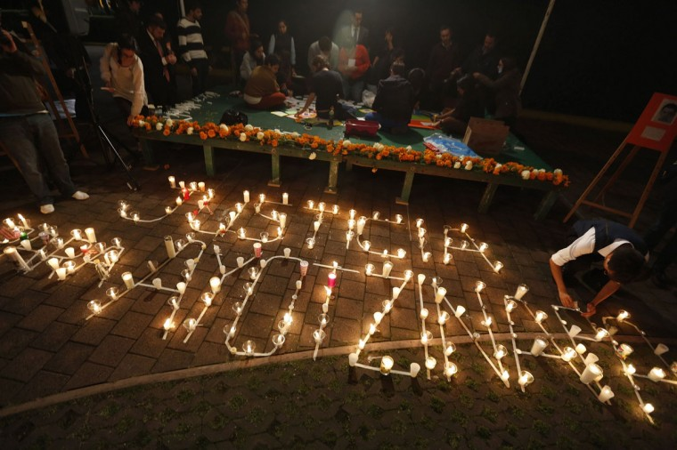 "Students at the Instituto Tecnologico Autonomo de Mexico (ITAM) in Mexico City arrange candles to form the words ""Justice for Ayotzinapa"" during a vigil for 43 Ayotzinapa students missing after last month's deadly clashes, October 14, 2014. On September 26, police allegedly linked to a criminal gang shot dead at least three students and abducted dozens of others during clashes in the southwestern city of Iguala. Forty-three of the students are still missing. (REUTERS/Tomas Bravo)"