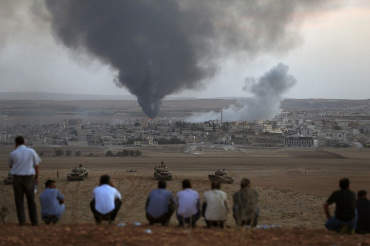Smoke rises in the Syrian town of Kobani as Turkish Kurds watch near the Mursitpinar border crossing on the Turkish-Syrian border in the southeastern town of Suruc October 9, 2014. Islamic State fighters seized more than a third of the Syrian border town of Kobani, a monitoring group said on Thursday, as U.S.-led air strikes failed to halt their advance and Turkish forces nearby looked on without intervening. (Umit Bektas/Reuters)