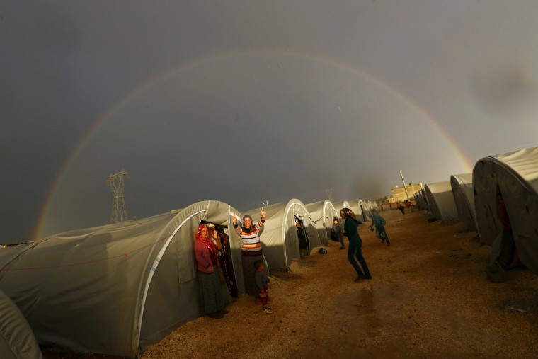 A Kurdish refugee from the Syrian town of Kobani shows victory sign as a rainbow forms over the camp in the southeastern town of Suruc, Sanliurfa province, October 16, 2014. The United States is bombing targets in Kobani for humanitarian purposes to relieve defenders of the Syrian town and give them time to organize against Islamic State militants, a senior U.S. official said on Wednesday. (Kai Pfaffenbach/Reuters)