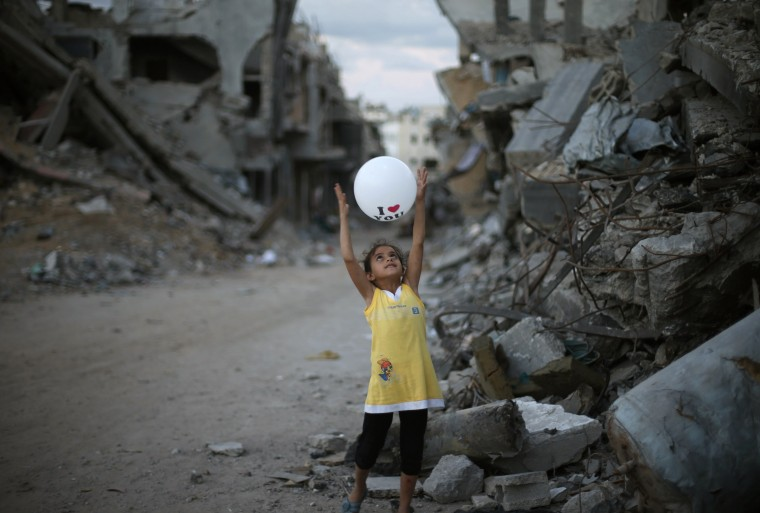 A Palestinian girl plays with a balloon near her family's house that witnesses said was destroyed during the seven-week Israeli offensive, in the east of Gaza City October 2, 2014. An open-ended ceasefire between Israel and Hamas-led Gaza militants, mediated by Egypt, took effect on August 26 after the seven-week conflict. It called for an indefinite halt to hostilities, the immediate opening of Gaza's blockaded crossings with Israel and Egypt, and a widening of the territory's fishing zone in the Mediterranean. (Suhaib Salem/Reuters)