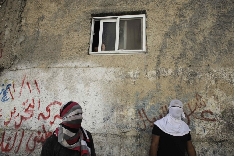 Palestinians stand below a window of a house during clashes with Israeli police in the Abu Tor neighbourhood of east Jerusalem October 30, 2014. Israeli police on Thursday shot dead Moataz Hejazi, a 32-year-old Palestinian suspected of having tried hours earlier to kill Yehuda Glick, a far-right Jewish activist, leading to clashes in East Jerusalem and fears of a new Palestinian uprising. REUTERS/Ammar Awad